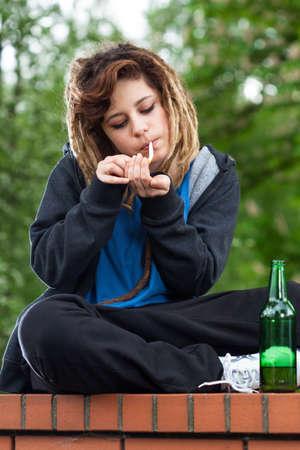 Rude rasta girl smoking and drinking beer on the wall Stock Photo