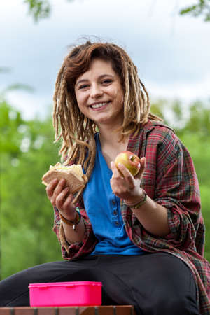 dreads: Cool girl with dreads eating lunch on the school break  Stock Photo