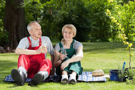 Gardener couple sitting on a blanket and drinking water photo