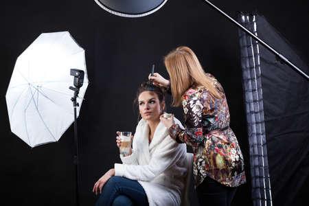 사진 촬영을 위해 여성 모델을 준비하는 메이크업 아티스트의 측면보기 스톡 콘텐츠