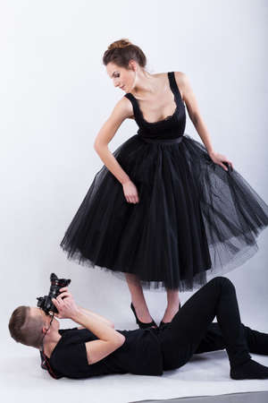 showbusiness: Photographer lying on the floor and taking a photo, vertical