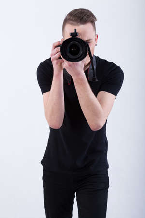 taking photograph: Photographer taking a photo on isolated white background Stock Photo