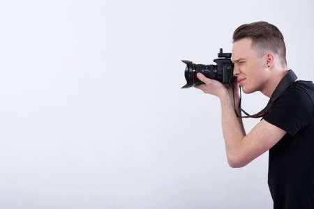 격리 된 흰색 배경에 젊은 사진 작가의 측면보기