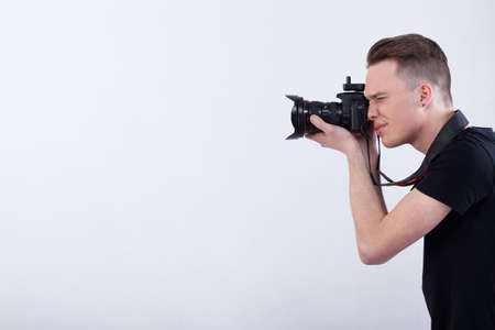 Side view of a young photographer on isolated white background photo