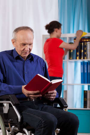 Woman cleans the house the disabled man, who reading a book photo
