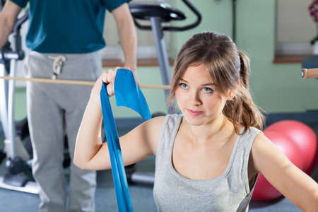 elastic: Beautiful girl exercising at physiotherapy clinic, horizontal Stock Photo