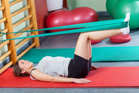 Girl lying on exercise mat and stretching legs with elastic band Imagens