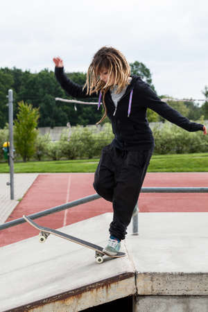 skateboarding tricks: Skate teenagirl with dreadlocks rides on a skateboard Stock Photo