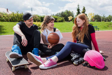 Youth baskatball players sitting on court and resting photo