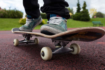 Young person rides on skateboard on court photo