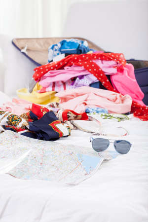 open suitcase: Holiday stuff lying on bed in mess