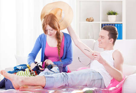 Young couple unpacking luggage and relaxing at hotel photo