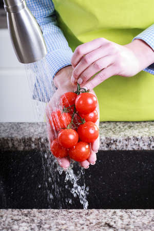 water sink: Housewife wash tomatoes in water in the sink