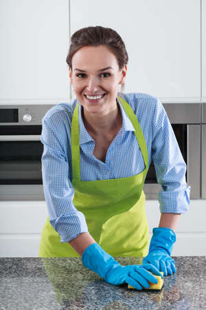countertops: Smiling housewife cleans the worktop in the kitchen Stock Photo