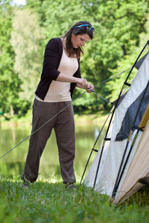 camping pitch: Girl trying to pitch a tent on a camping