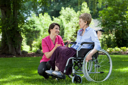 Woman on wheelchair relaxing in garden with nurse Stock Photo