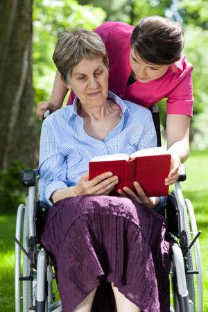 handicap: Woman on wheelchair reading book in a garden Stock Photo