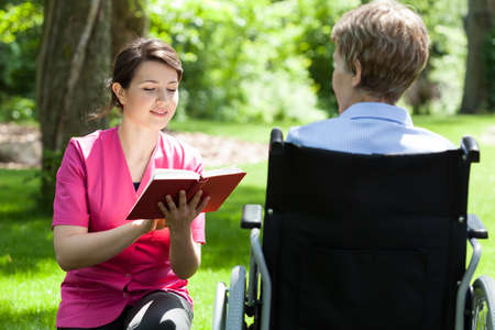 Nurse reading book next to disabled woman