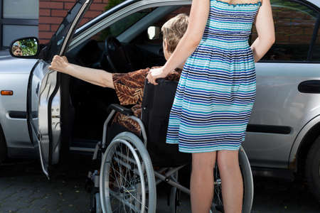 Woman helping disabled lady get into the car photo