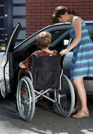 Disabled lady and her daughter next to car photo