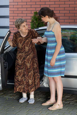 Elderly lady after driving in front of house photo