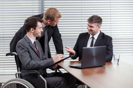 Happy disabled man during business meeting, horizontal photo