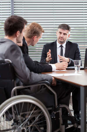 Disabled employee next to conference table, vertical photo