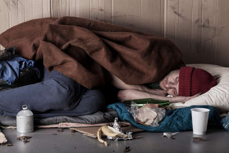 alcohol cardboard: Horizontal view of a poor man sleeping on the street
