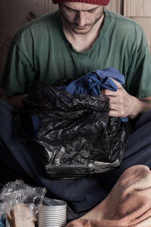 miserable: Vertical view of a poor man with garbage bag in hand Stock Photo