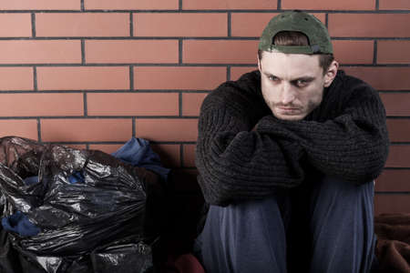 destitution: Poor man sitting hunched on the ground around the trash bags