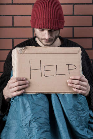 mendicant: Homeless young man begging on the street with help sign