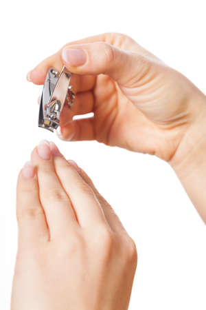 nail clippers: Hand with nail clippers on isolated background Stock Photo