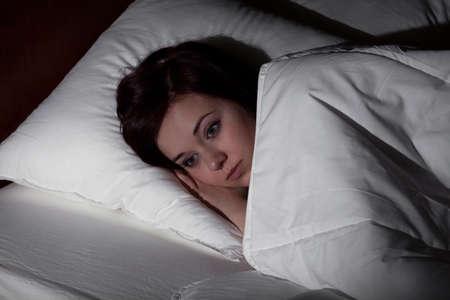 insomnio: Mujer joven que sufre de insomnio tumbado en la cama por la noche