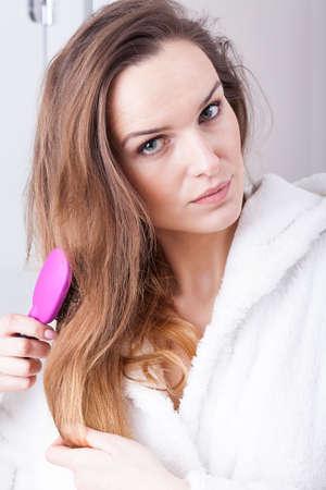combing hair: Beautiful woman combing hair during morning bath
