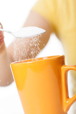 sweeten: Hand sweetening hot drink on isolated background Stock Photo