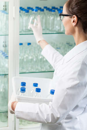 Lab assistant in white apron putting glass bottle into cabinet photo