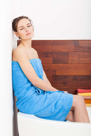 Beauty lady in blue towel sitting on bath and relaxing photo
