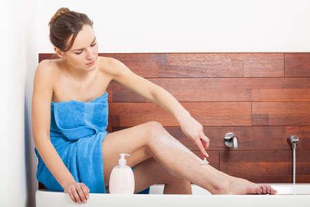 Beautiful young woman shaving legs in bathroom Stock Photo