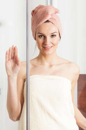 Pretty young woman in towel after shower smiling photo