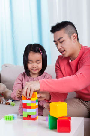 Asian family playing with blocks in a living room