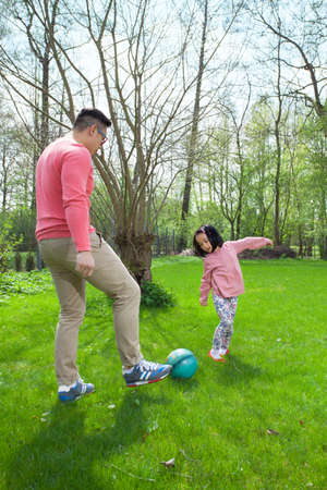 Asian family playing football in a garden