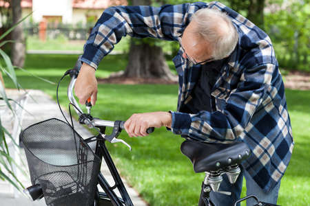 Handyman repairing bicycle handlebar in the backyard photo