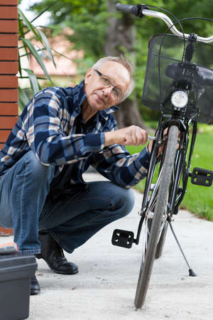 Vertical view of a elderly man fixing bicycle photo