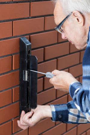 Senior man repairing gate lock with screwdriver photo