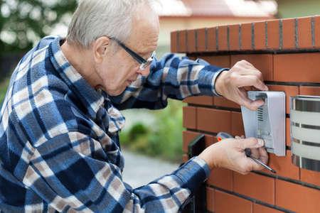 Handyman in flannel shirt fixing intercom, horizontal