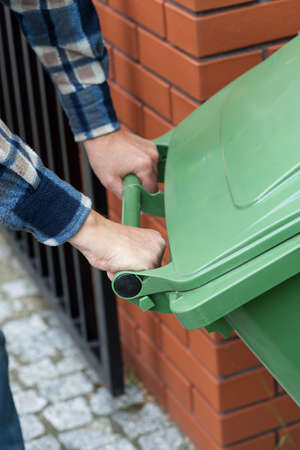 dumpster: Close-up of a male hands pushing a wheeled dumpster Stock Photo