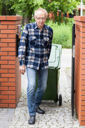 wheeled: Elderly man pulling a wheeled dumpster, vertical