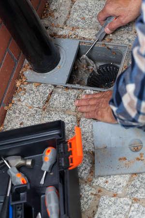 desague: Primer plano de un Hombre manos limpieza orificio de drenaje del pavimento