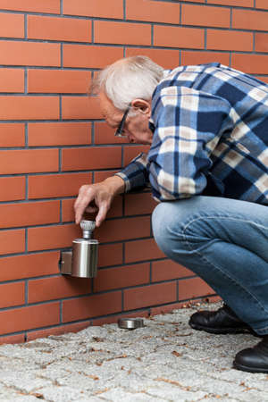 home  lighting: Old man changing the light bulb outside