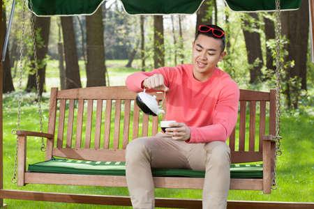 Asian man drinking tea in a garden photo